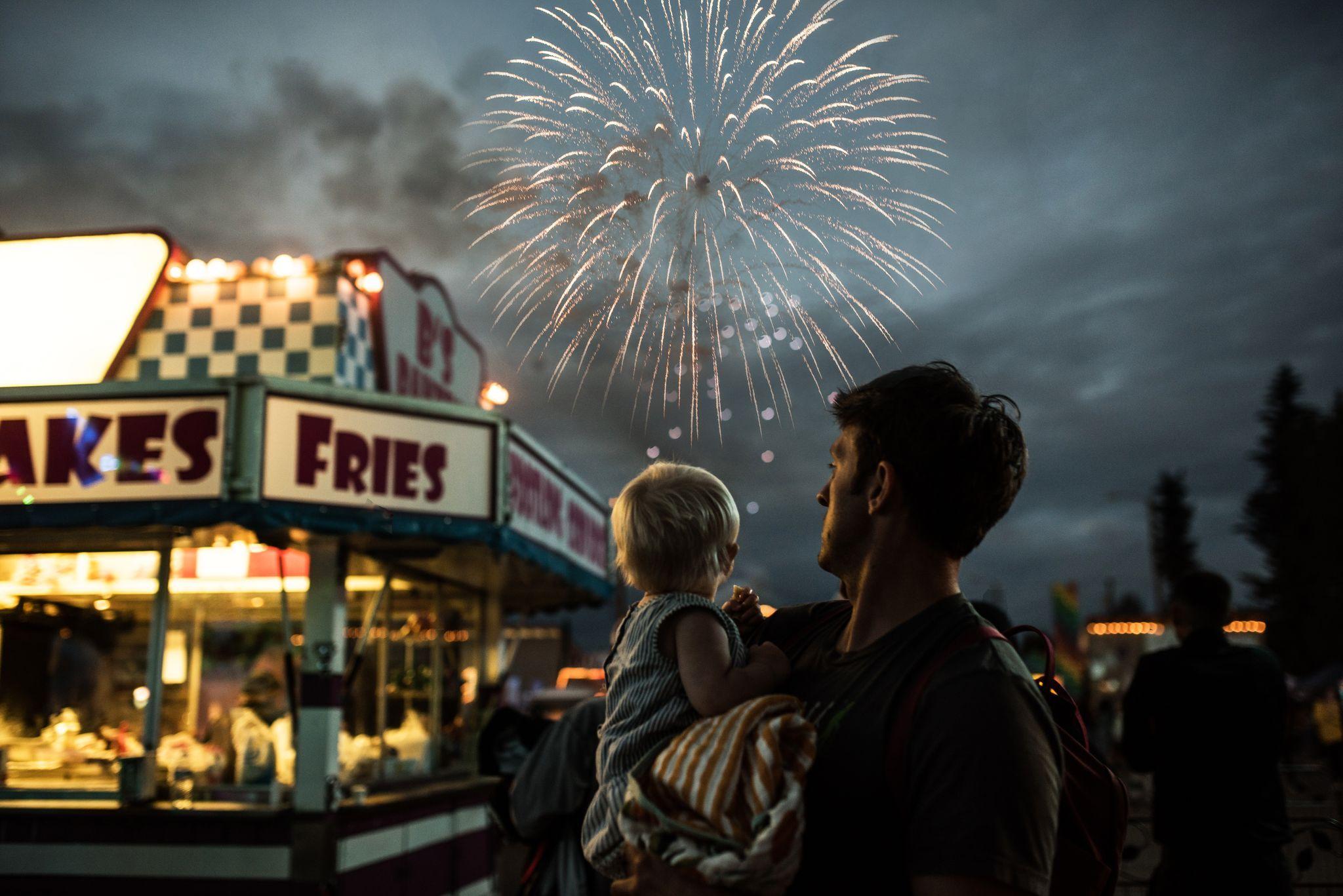پدری با پسر خردسالش در حال تماشای آتشبازی در نمایشگاه ایالتی آلاسکا که در یک لحظه شکار دوربین عکاس شده است. عکاس: LINDSAY SAUNDERS